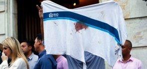 José Gerson da Silva, pai do menino Marcos Vinícius, exibe camiseta da escola manchada de sangue no enterro do filho no Rio de Janeiro
