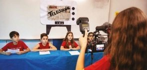 Foto de quatro alunos sentados. No fundo, está escrito telejornal. Na frente, alguém filma