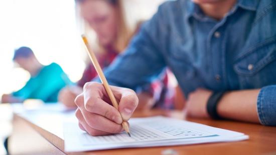 mão segurando lápis preenchendo folha de papel apoiada em mesa de madeira