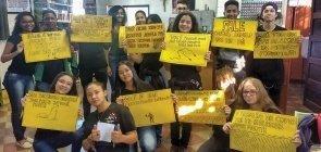 Grupo de alunos segurando cartazes amarelos com mensagens