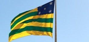Bandeira listrada verde e amarela com um quadrado azul no canto superior direito com estrelas brancas