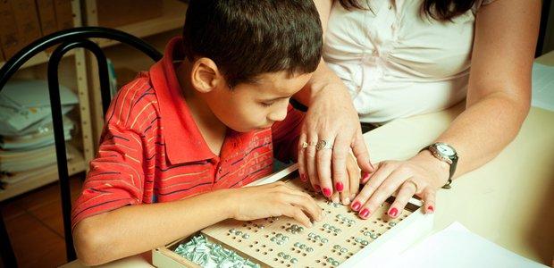 Isac Oliveira Souza aprendendo ler na lousa de braile, na sala de recursos da EE Dom Jayme de Barros, coordenada pela professora Luiza Helena Tristão. Foto: Patrícia Stavis
