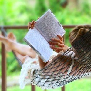 O que ler durante as férias_mulher lendo deitada em rede