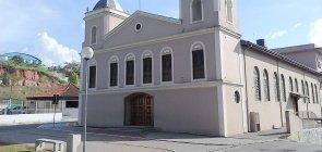 Fachada de igreja com paredes cinza e detalhes em branco