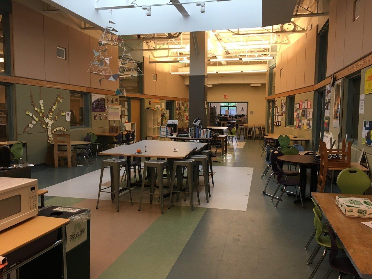 Na imagem, vista da entrada da Acera School, com várias mesas grandes.