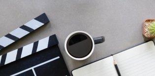 uma composição sobre uma mesa branca vista de cima com uma claqueta de cinema, um vaso pequeno de cactus, um lápis, um caderno e uma caneca de café