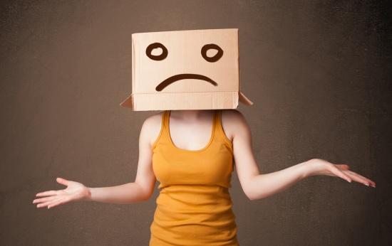 Mulher com uma caixa na cabeça cobrindo seu rosto e um desenho de carinha triste na caixa