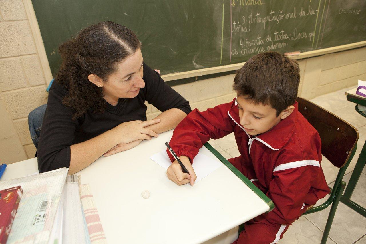 Professora está sentada à mesa com um aluno. Ela olha para ele, enquanto ele escreve uma lista de palavras durante uma sondagem (Crédito: Mariana Pekin)