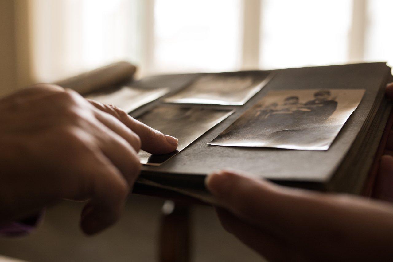 Mãos seguram um álbum e apontam para velhas fotos de família