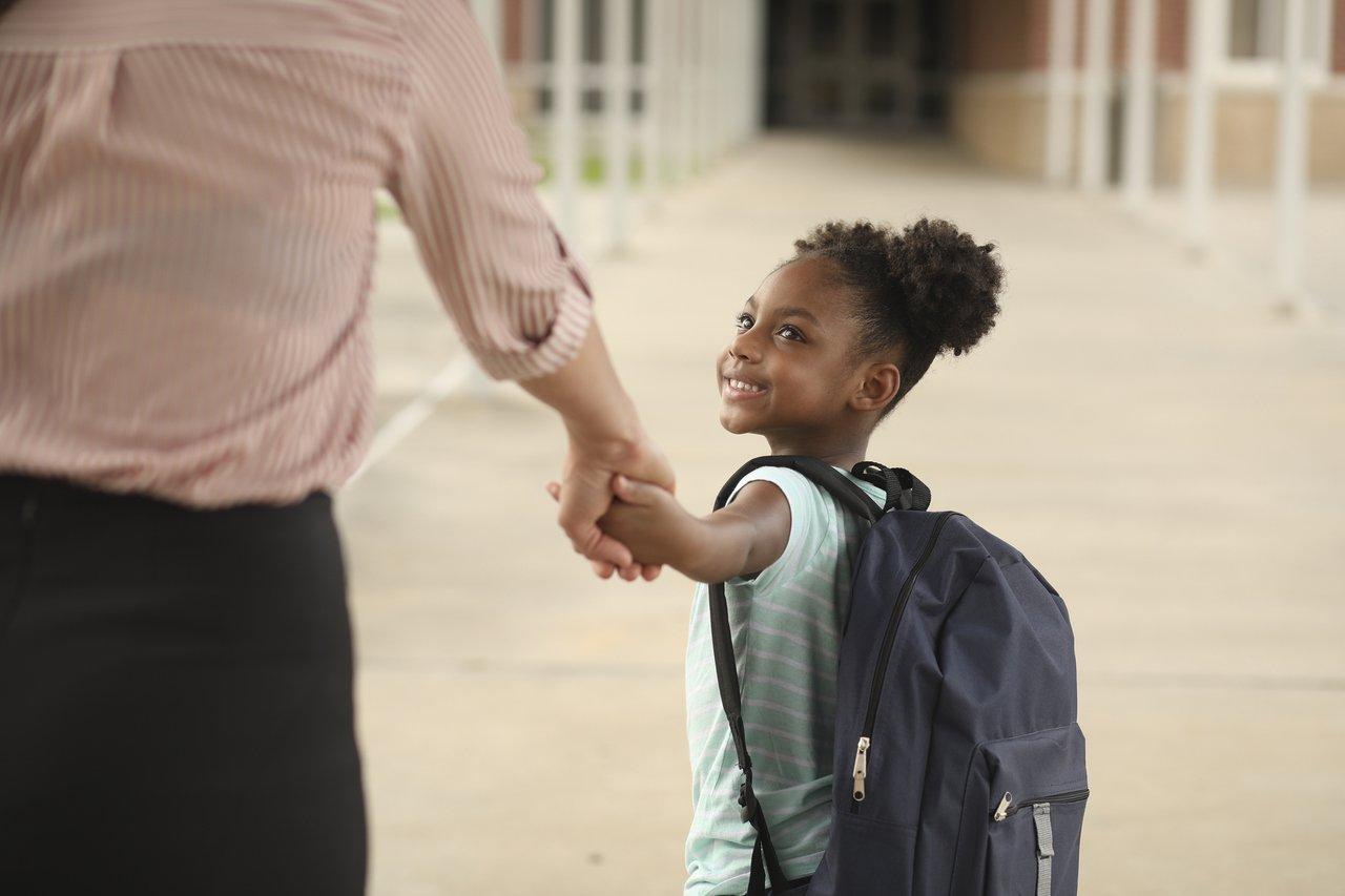 garota de mãos dadas com responsável, no fundo a escola