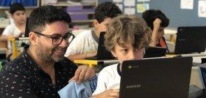 Professor Marcio Gonçalves discute a produção com aluno, com apoio do computador