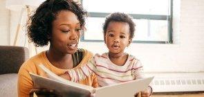Mulher estimula bebê com leitura de livro infantil