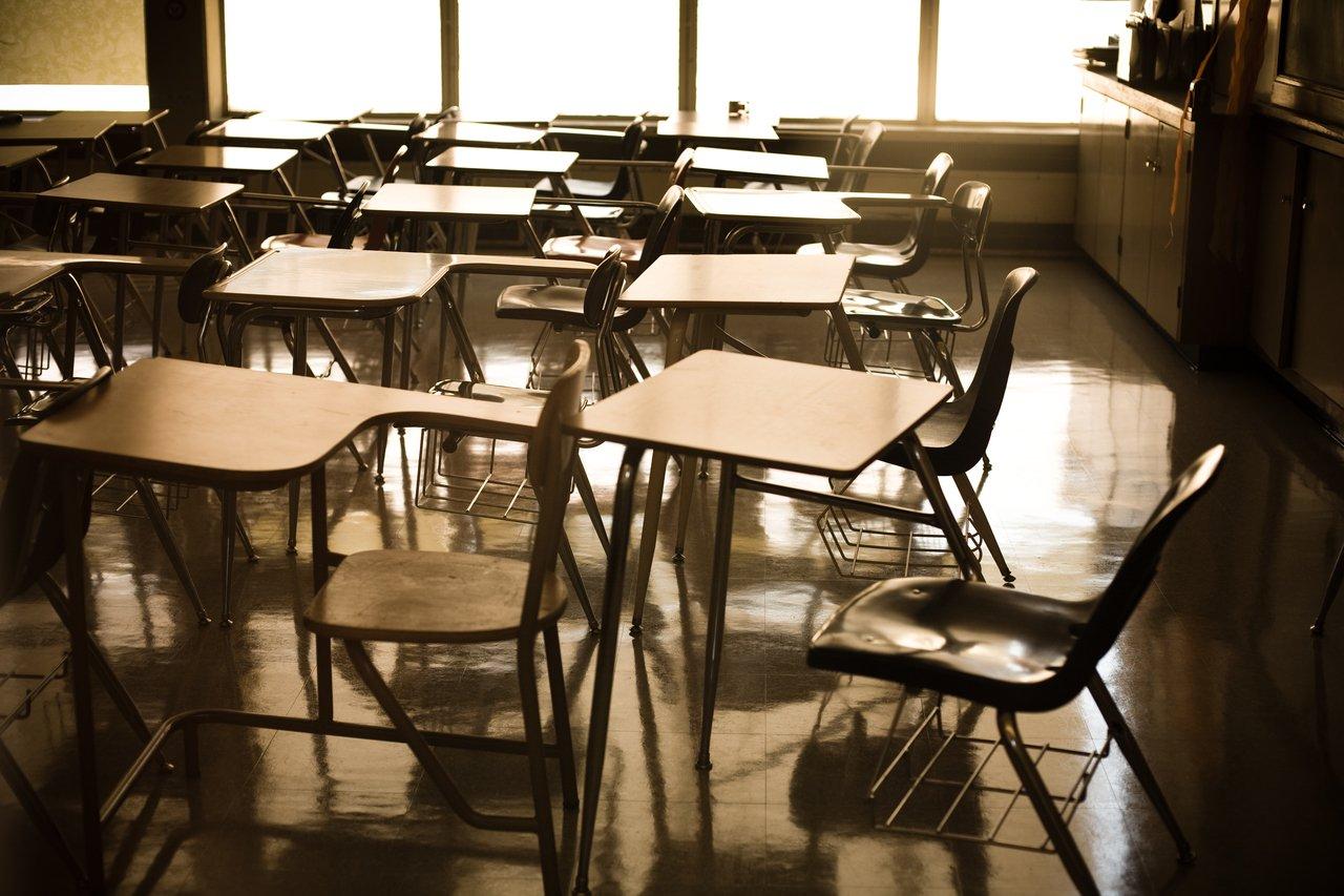 Sala de aula vazia com carteiras e cadeiras amontoadas em frente a uma janela com luz indireta