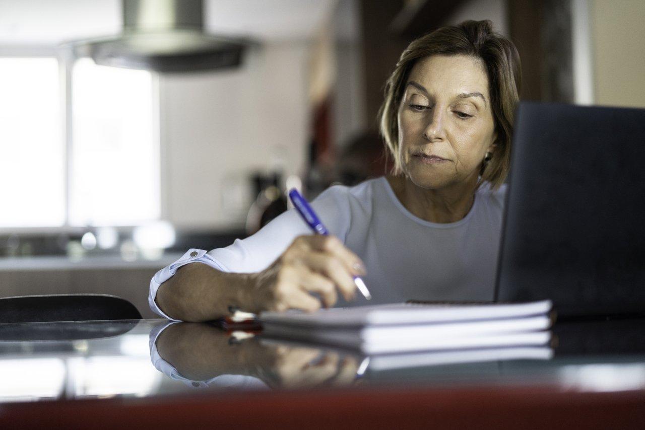 mulher com lápis na mão escrevendo em papel, na mesa também tem um notebook