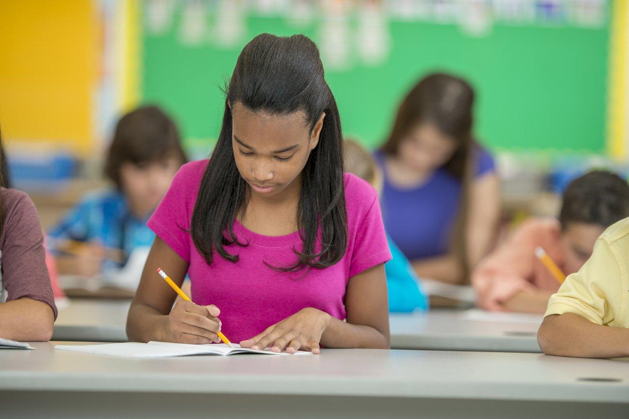 Aluna vestindo blusa rosa escreve em um papel com um lápis laranja, sentada em uma sala de aula