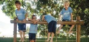 Quatro crianças escalam brinquedão. Elas usam uniforme, uma camiseta azul claro escrito Maristas e uma bermuda azul escuro
