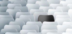 Conjunto de cadeiras brancas. Ao centro, uma cadeira de encosto preto se destaca.