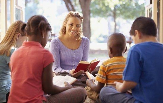 Professora em sala de aula lendo para alunos