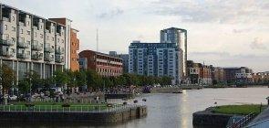 Alguns prédios localizados nas margens de um rio na cidade de Limerick, na Irlanda