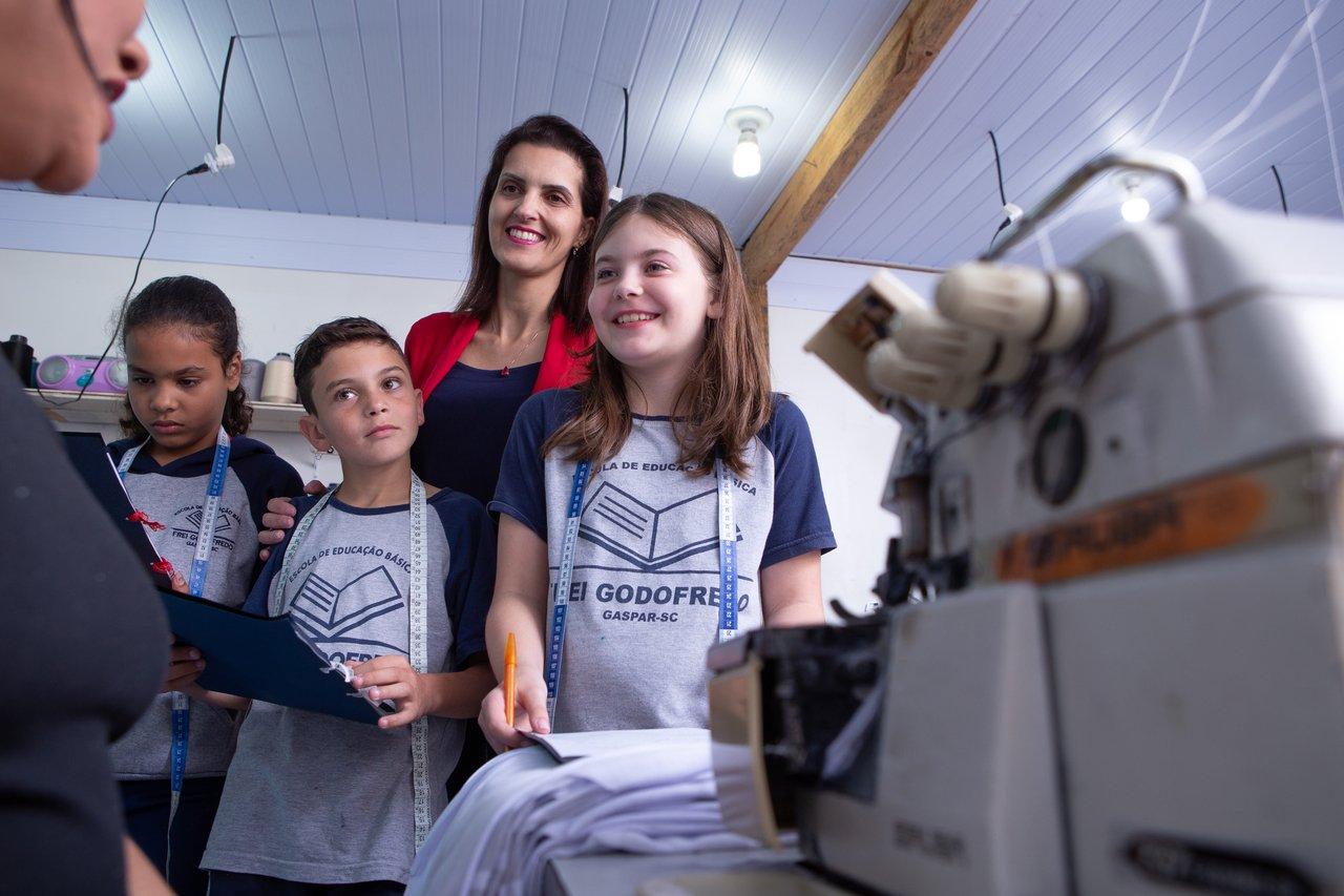 A professora Jussara Schmitz e seus alunos visitam uma oficina de costura em Gaspar (SC) para o projeto Costurando a Matemática