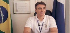 Secretário estadual do Rio de Janeiro vestindo camiseta branca e crachá da secretaria sentado em sua mesa com bandeira do Brasil e certificados ao fundo