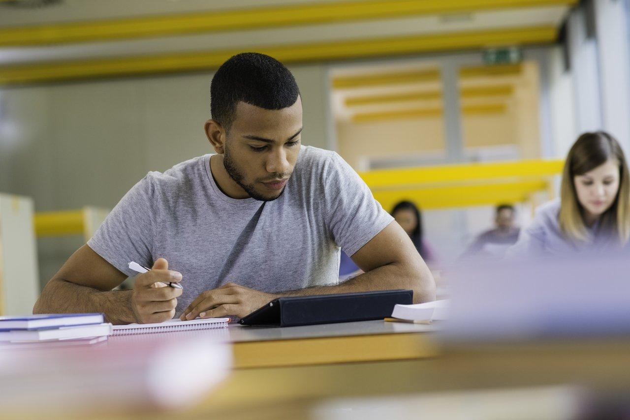 Estudante sentado em uma sala de aula concentrado nos livros escreve em um caderno