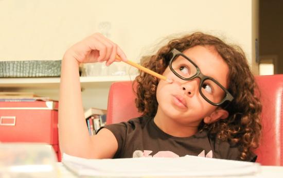 Menina de cabelos cacheados e óculos em dúvida apoiando-se em um lápis