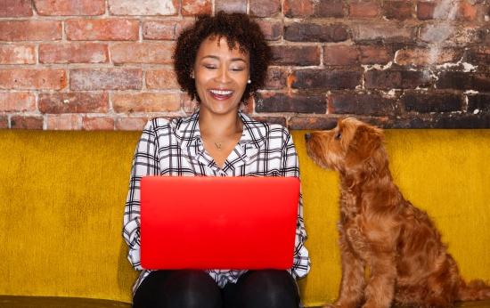 Mulher sentada no sofá mexendo em um computador vermelho sendo observada por um cachorro