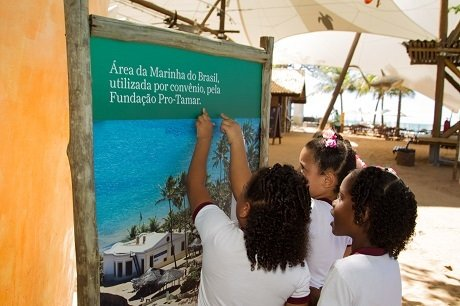 """Três crianças de cerca de 8 anos apontam o dedo para uma placa que diz """"área da marinha do Brasil, utilizada por convênio pela Fundação Pro-Tamar"""""""