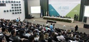 Foto da perspectiva da plateia da audiência pública da Base em Olinda. Ao fundo, vê-se uma mesa com membros do MEC e CNE