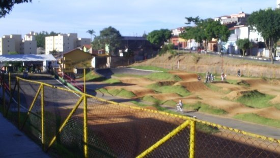 O primeiro plano mostra uma grade amarela. Atrás dela, revela-se uma área verde coberta por grama com ondulações no solo.