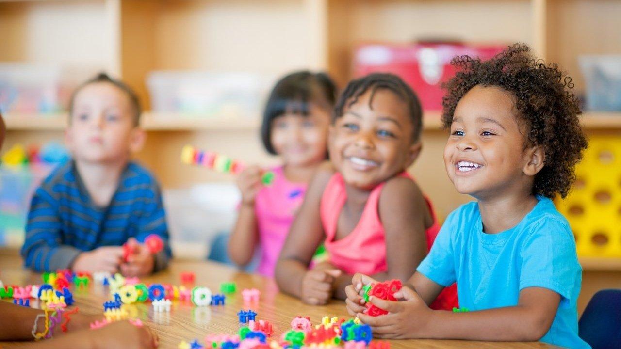 Quatro crianças de cerca de três anos brincando sentados em volta de uma mesa