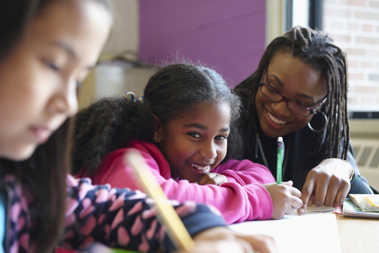 Aluna olha para a câmera, sentada em uma carteira de escola, ajudada por uma professora