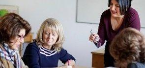 Três professoras de cerca de 40 anos sentadas juntas em uma mesa com uma quarta mulher de pé olhando as atividades