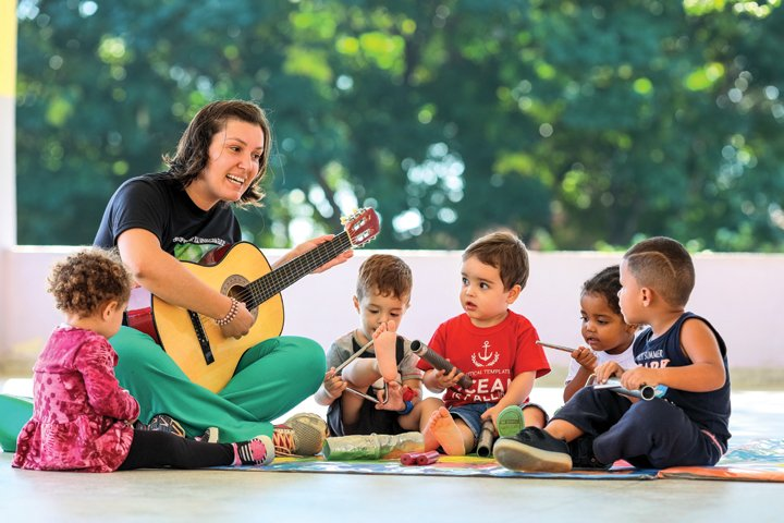 Professora Ariana está sentada em roda com quatro alunos. Ela segura um violão e canta cantigas para os pequenos.