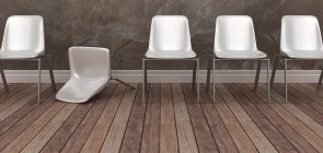 Cadeira branca caída em meio a fileira com outras cadeiras em sala com parede de concreto