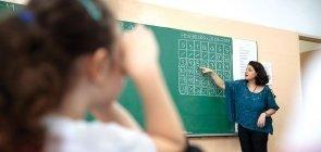 Professora aponta para calendário de fevereiro escrito na lousa verde