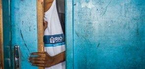 Uma porta azul desgastada, entreaberta vemos um aluno com o uniforme da prefeitura do Rio de Janeiro