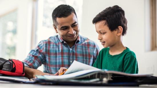 Menino de camisa verde sorri diante de caderno de lição de casa sobre mesa branca, ao lado do pai, que usa camisa xadrez azul e vermelha e também sorri