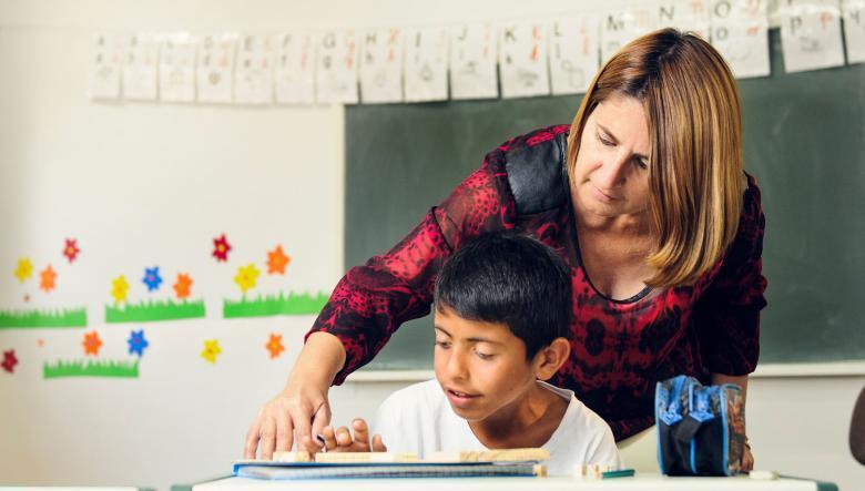 Professor interagindo com aluno em sala