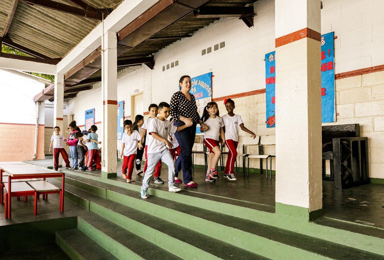 Mara Mansani caminha de mãos dadas com as crianças de sua sala pelo pátio da escola em Sorocaba (SP)