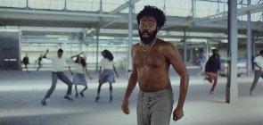 Trecho do videoclipe This is America do Childish Gambino. Na foto aparece ele no meio, homem negro ao redor dos 30 anos, sem camisa, usa uma calça social cinza. No fundo jovens com uniformes dançam