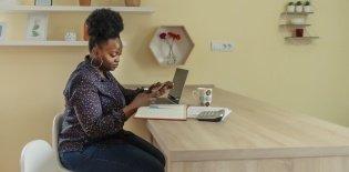 Diretora olha o celular enquanto trabalha no computador
