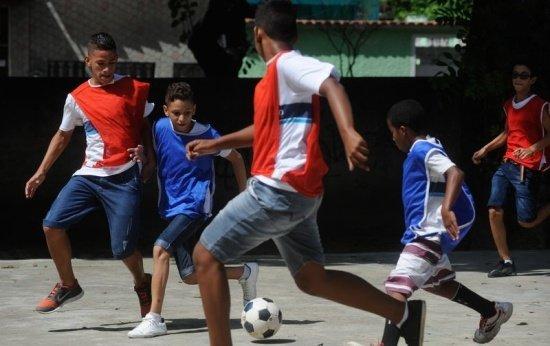 Cinco meninos jogam futebol na escola. Eles estão vestidos com coletes de duas cores diferentes