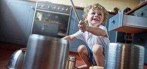 um menino de cerca de cinco anos usando utensílios de cozinha para batucar nas panelas que estão no chão. A foto foi feita em uma cozinha.