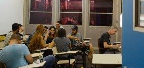 Estudantes universitários conversam em sala de aula