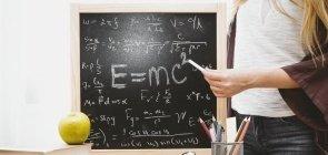Foto de uma lousa com a equação e=mc² e uma menina segura um giz