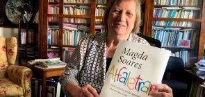 Professora Magda Soares segura a capa de seu novo livro