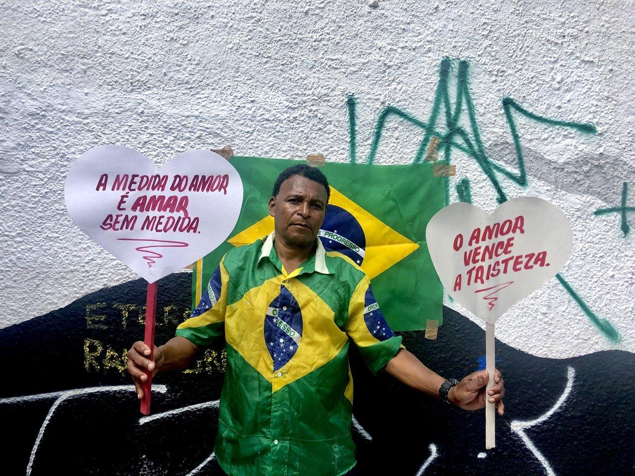 Um homem de cerca de 60 anos vestindo uma camiseta com a bandeira do Brasil e segurando dois corações de papel