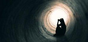 Menina sentada dentro de um túnel escuro